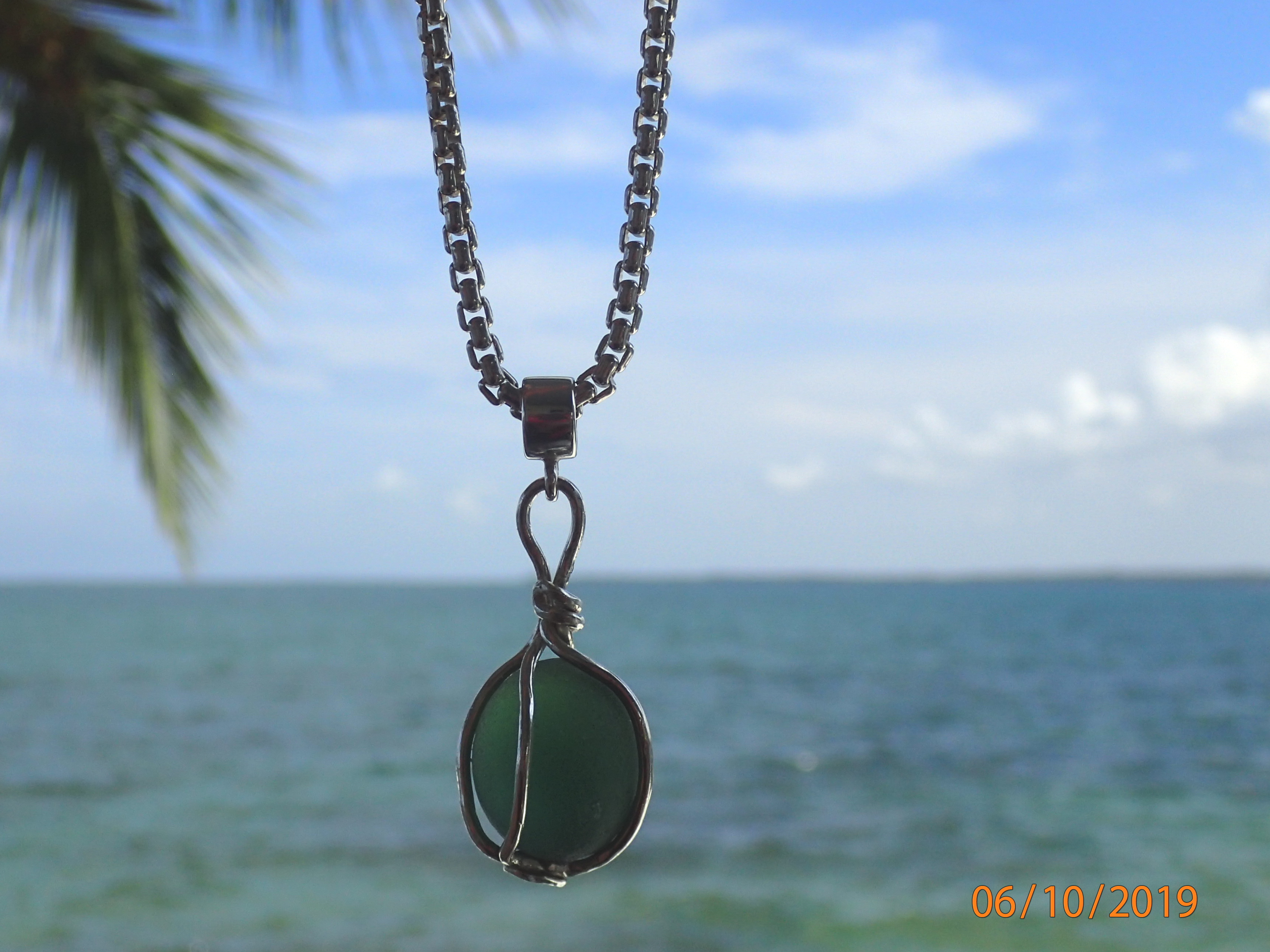 Deep green circular antique seaglass nugget like an antique glass float caged in a sophisticated sterling silver frame.